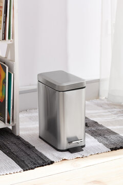Subject shot of lidded hands-free wastebasket with foot pedal. The stainless steel trash can is located on striped white and gray carpet near bookshelf in the light room.