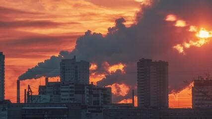 Fotobehang - Smokestacks emitting smoke pollution over sunset city skyline silhouette. Zoom out. 4K UHD Timelapse.