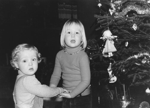 December 1977 vintage, retro monochrome image of a brother and sister, holding hands, standing next to a vintage decorated christmas tree.