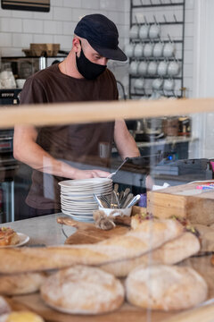 Male barista wearing black baseball cap and face mask working behind counter.