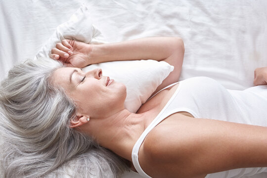 Mature attractive Caucasian woman sleeping on white sheets