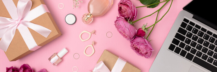 Banner with gift, laptop, flowers, feminine cosmetics and accessories on a pink background. Online...