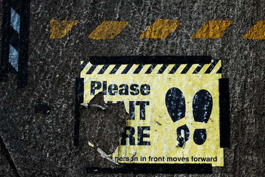 High angle close up of black and yellow 'Please Wait Here' sign on asphalt ground.