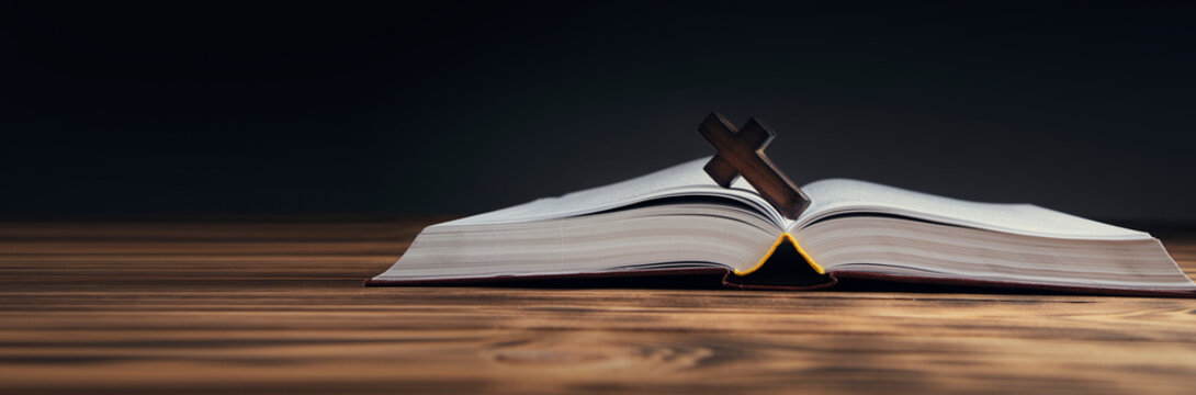 wooden cross on open Bible