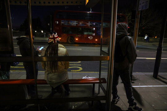People wait at a bus stop on Putney Bridge which is usually full with traffic as Britain began its third COVID-19 lockdown