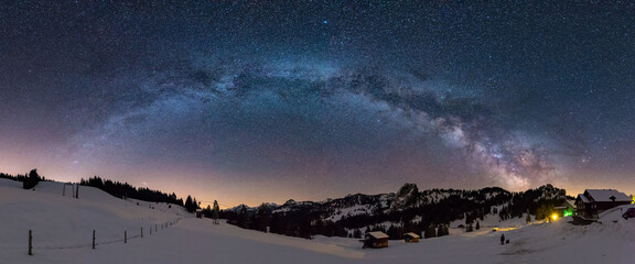 Panoramic shot of mountains under a starry night sky in winter