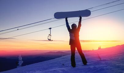 Silhouette of snowboarder against setting sun in lift ski resort