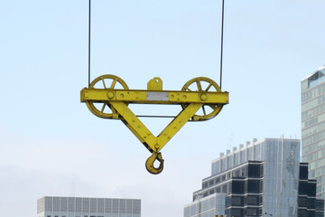 close up of a yellow hook block of a tower crane on a construction site