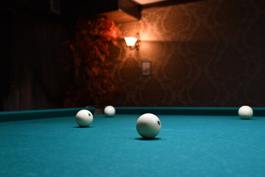 The pool balls are on the green table. Playing pool