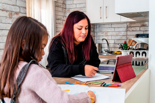 Latin woman studying with her daughter at home