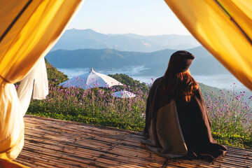 Rear view image of a woman sitting on wooden balcony while watching a beautiful mountains and...