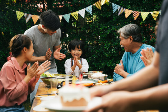 Family celebrate birthday party with cake outdoors.
