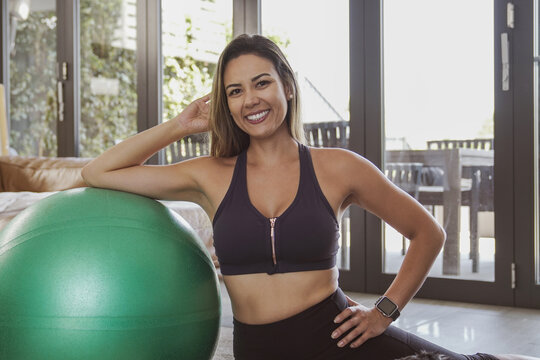 Portrait of beautiful Brazilian woman in sportswear with fitness ball, home exercise workout, online fitness class concept
