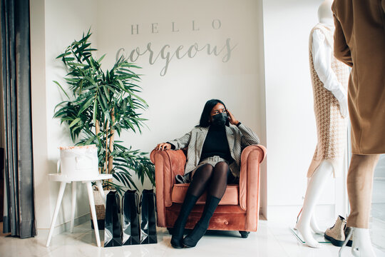 elegant and fashionable black woman with face mask sitting indoor in a luxury fashion shop looking outside to the street