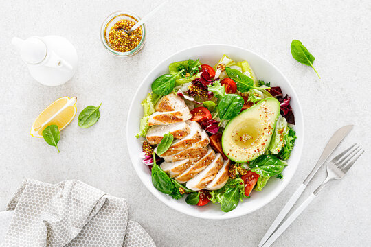 Grilled chicken meat and fresh vegetable salad of tomato, avocado, lettuce and spinach. Healthy and detox food concept. Ketogenic diet. Buddha bowl dish on white background, top view