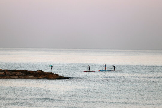 People paddle on stand-up boards in the Mediterranean Sea, as seen from a beach in Tel Aviv