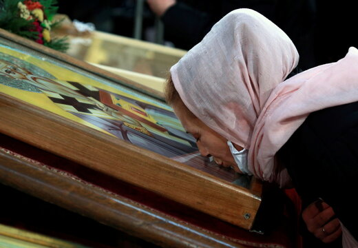 A woman kisses an icon during the Orthodox Christmas mass at St Kliment Orthodox church in Skopje