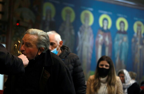 A man kisses a cross during the Orthodox Christmas mass at St Kliment Orthodox church in Skopje