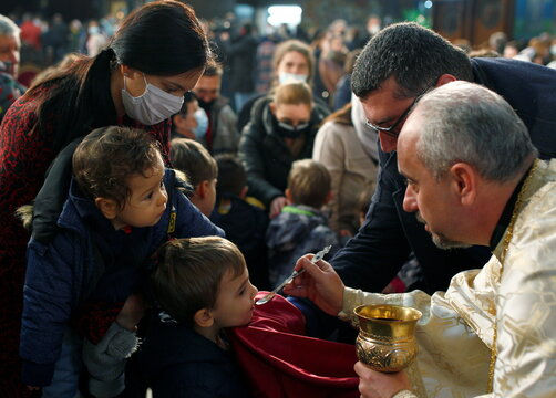 A faithful receives sacraments during the Orthodox Christmas mass at the St. Klement Cathedral  in Skopje