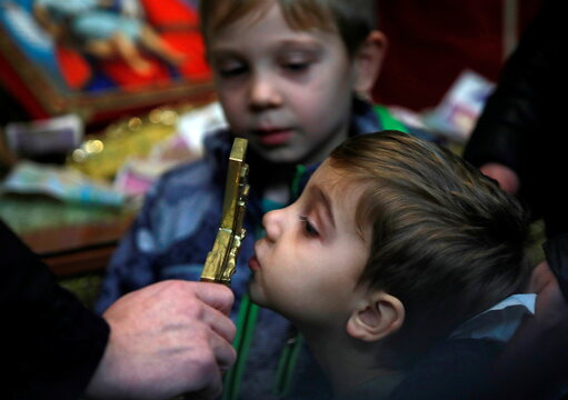 A boy kisses a cross during the Orthodox Christmas mass at St Kliment Orthodox church in Skopje