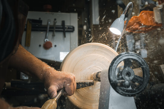 a man in a working apron works on a wood turning lathe. hands hold a chisel. hobby