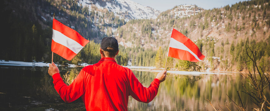 male hiker is holding two austrian flags and is standing in front of mountain lake somewhere in the alps
