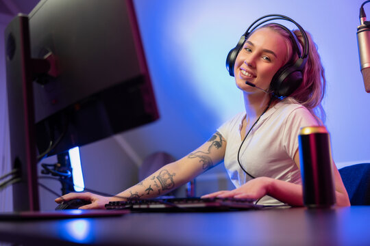 Smiling e-sport gamer girl vlogging and plays online video game on PC