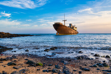 Old wrecked ship in blue ocean, in the town of Arrecife on the island of Lanzarote