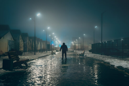 Silhouette of dark man in hood in night illuminated city alley in foggy weather, misty horror and scary atmosphere concept.