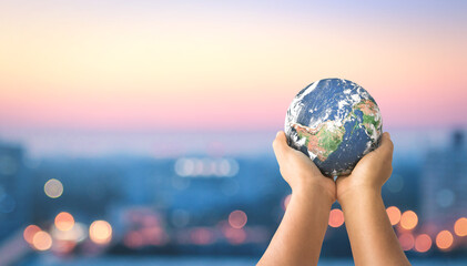 Donation for Covid 19 concept:  Human hands holding earth global over blurred city night background. Elements of this image furnished by NASA
