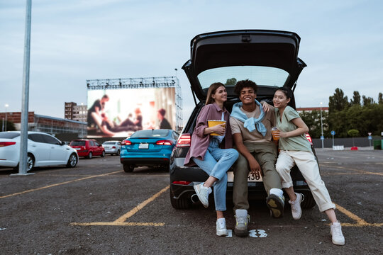 Young multiracial people in trunk on parking at auto cinema