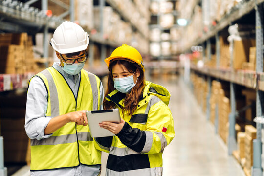 Asian engineer man and woman in helmets in quarantine for coronavirus wearing protective mask working in new normal at shelves with goods background in warehouse.logistic and business export