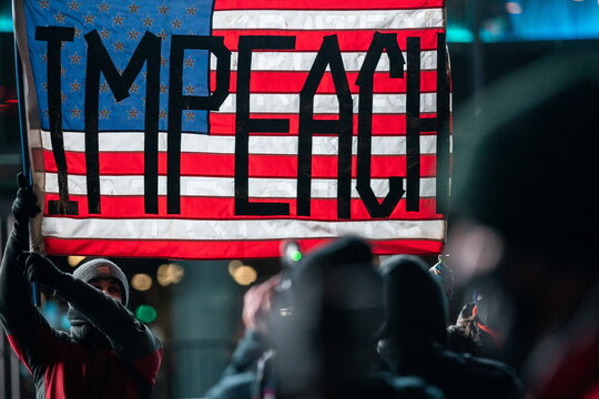"""People wearing protective masks hold a U.S. flag at the Barclays Center during the """"Get him out! defend democracy"""" rally in the Brooklyn borough of New York City"""