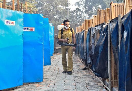 A man sanitizes a toilet area at a base camp where pilgrims gather before heading for an annual trip to Sagar Island, in Kolkata