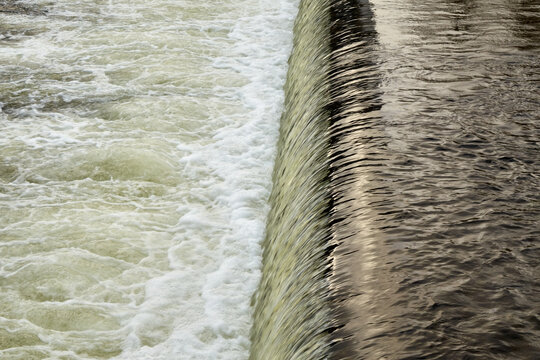 Water cascading over a weir on a small river