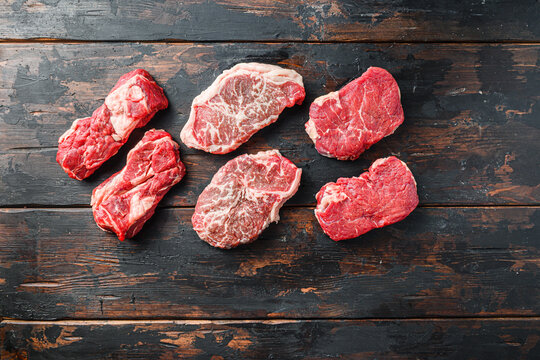 Variety of organic raw beef steakes rump, chuck roll and top blade  cut  on old rustic dark wooden background, top view with space for text.