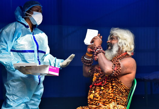 A Sadhu or a Hindu holy man reacts before a healthcare worker wearing PPE will collect a swab sample from him for a rapid antigen test at a base camp, in Kolkata