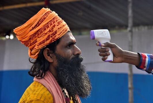 A Sadhu or a Hindu holy man gets his temperature measured at a base camp, in Kolkata