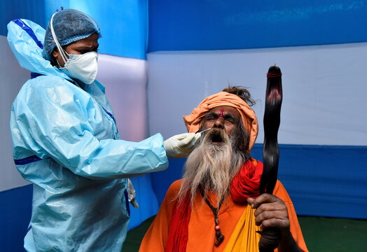 A Sadhu or a Hindu holy man reacts as a healthcare worker wearing PPE collects a swab sample from him for a rapid antigen test at a base camp , in Kolkata