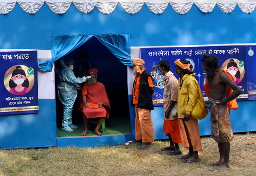 A healthcare worker wearing PPE collects a swab from a Sadhu or a Hindu holy man for a rapid antigen test at a base camp, in Kolkata