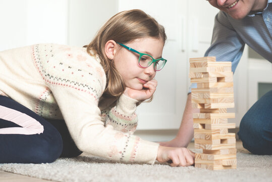 Happy father playing with cute daughter with wooden blocks at home