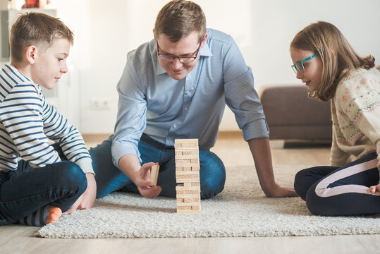 Young happy father playing with his two cute children with wooden blocks