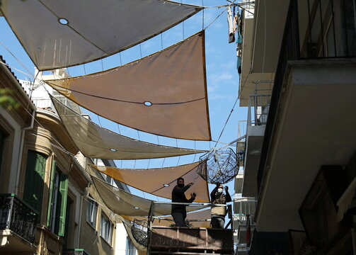 Workers wearing protective masks remove Christmas decorations, amid the coronavirus disease (COVID-19) pandemic in Nicosia