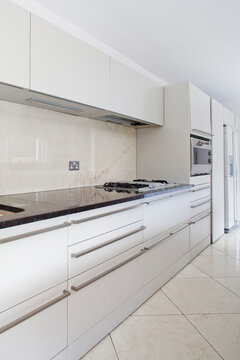 Modern kitchen with white units and tiled floor