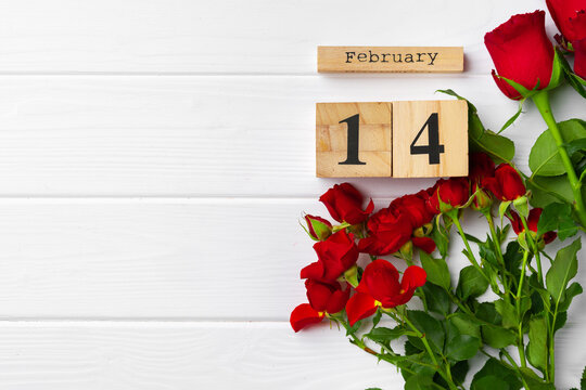 Wooden calendar 14th February and roses on white background
