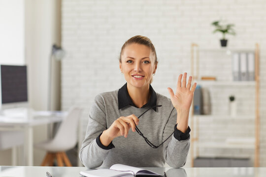 Happy young woman sitting at desk, waving hand at camera. School teacher, online tutor, university professor, college student, businesswoman, vlogger or remote worker says hello in video call meeting