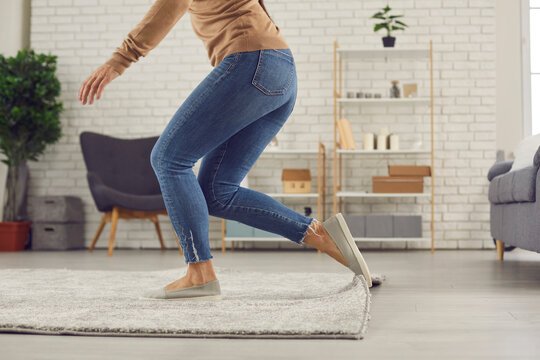 Unrecognizable female trips over rug. Clumsy faceless woman in uncomfortable shoes stumbles on rug in living-room and is about to fall on floor. Domestic accidents and getting injured at home concept