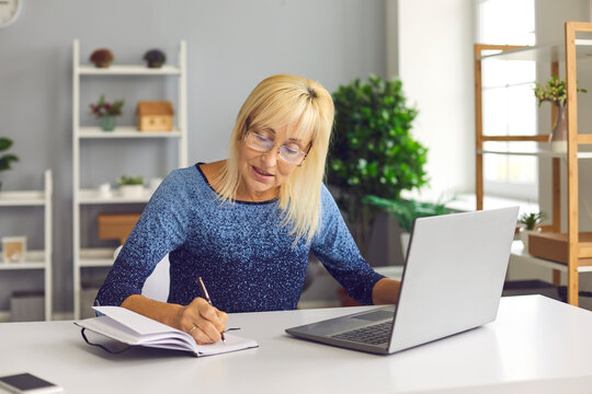 Senior woman making notes in notebook while looking at business training or online webinar on laptop. Concept of remote work or social distance learning at home.