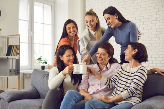 Group of happy young women having fun and enjoying time together. Smiling friends or colleagues sitting on sofa at home or in office, laughing at funny joke, clinking cups and drinking coffee or tea