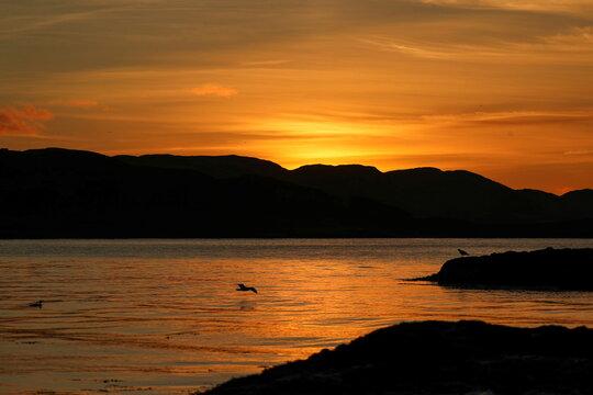 The sun sets behind Kerrera island near Oban